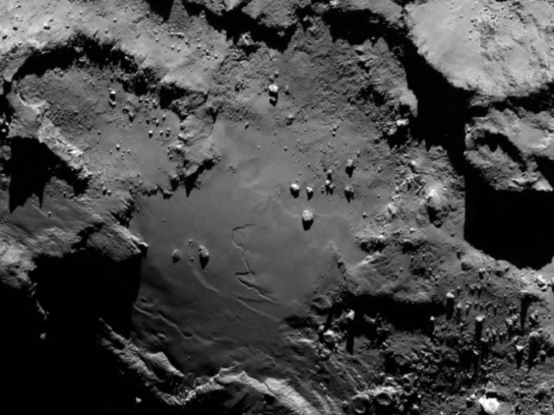 Stunning close up detail focusing on a smooth region on the 'base' of the 'body' section of comet 67P/Churyumov-Gerasimenko. The image clearly shows a range of features, including boulders, craters and steep cliffs. Credit: ESA/Rosetta/MPS for OSIRIS Team