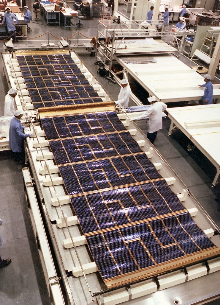 A solar cell blanket deployed on a water table during the Solar Array deployment test. The Hubble Solar Arrays provide power to the spacecraft. The arrays are mounted on opposite sides of the HST, on the forward shell of the Support Systems Module. Each array stands on a 4-foot mast that supports a retractable wing of solar panels 40-feet (12.1-meters) long and 8.2-feet (2.5-meters) wide, in full extension. The arrays rotate so that the solar cells face the Sun as much as possible to harness the Sun's energy. The Space Telescope Operations Control Center at the Goddard Space Center operates the array, extending the panels and maneuvering the spacecraft to focus maximum sunlight on the arrays. The HST Solar Array was designed by the European Space Agency and built by British Aerospace.