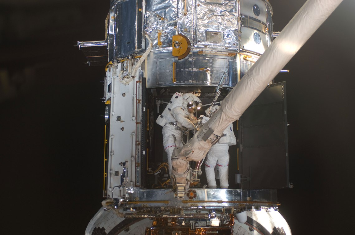 Astronauts Michael Good (left) and Mike Massimino, both STS-125 mission specialists, participate in the mission's fourth session of extravehicular activity (EVA) as work continues to refurbish and upgrade the Hubble Space Telescope. During the eight-hour, two-minute spacewalk, Massimino and Good continued repairs and improvements to the Space Telescope Imaging Spectrograph (STIS) that will extend the Hubble's life. Credit: NASA
