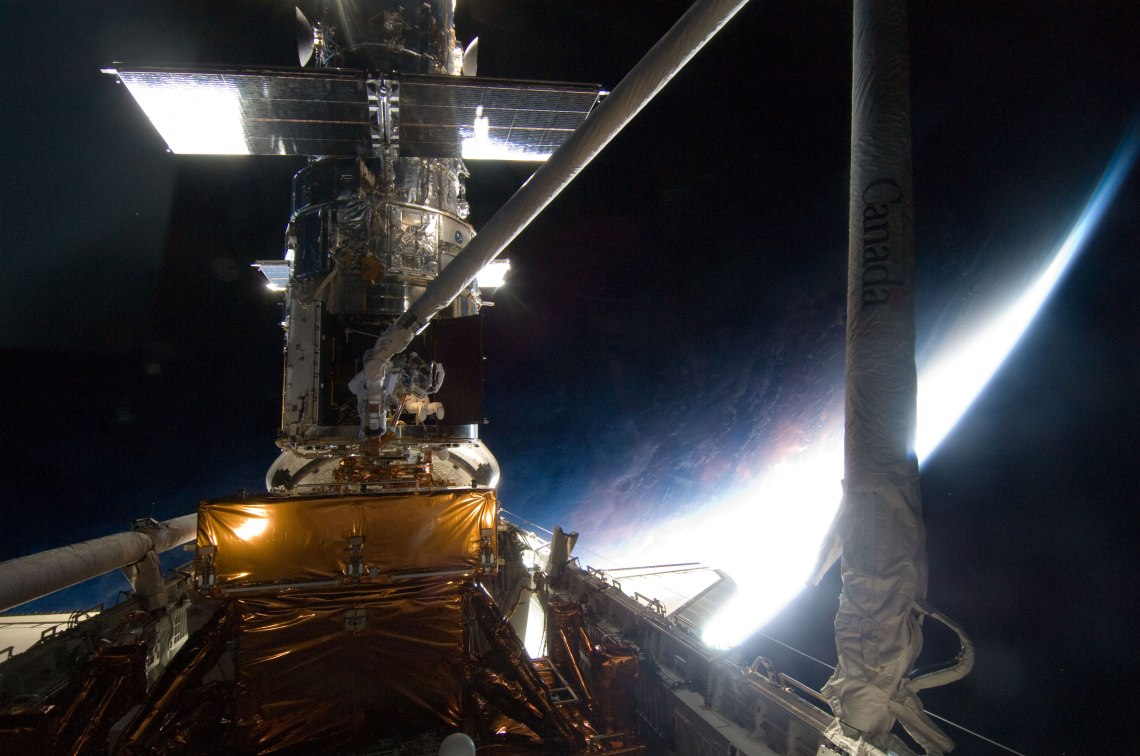 With a mostly dark home planet behind him, STS-125 mission specialist Michael Good rides Atlantis' remote manipulator system arm to where he needs be while working on the Hubble Space Telescope.  Credit: NASA
