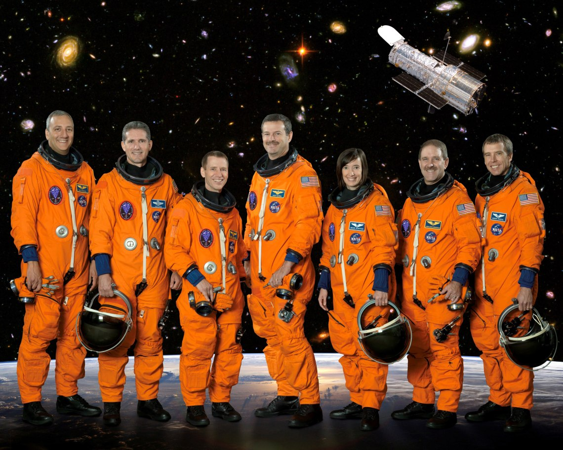 Posing for the STS-125 crew portrait, from left, are astronauts Michael J. Massimino, Michael T. Good, both mission specialists; Gregory C. Johnson, pilot; Scott D. Altman, commander; K. Megan McArthur, John M. Grunsfeld and Andrew J. Feustel, all mission specialists. The STS-125 mission was the final Space Shuttle mission to visit the Hubble Space Telescope for repairs and upgrades. Credit: NASA