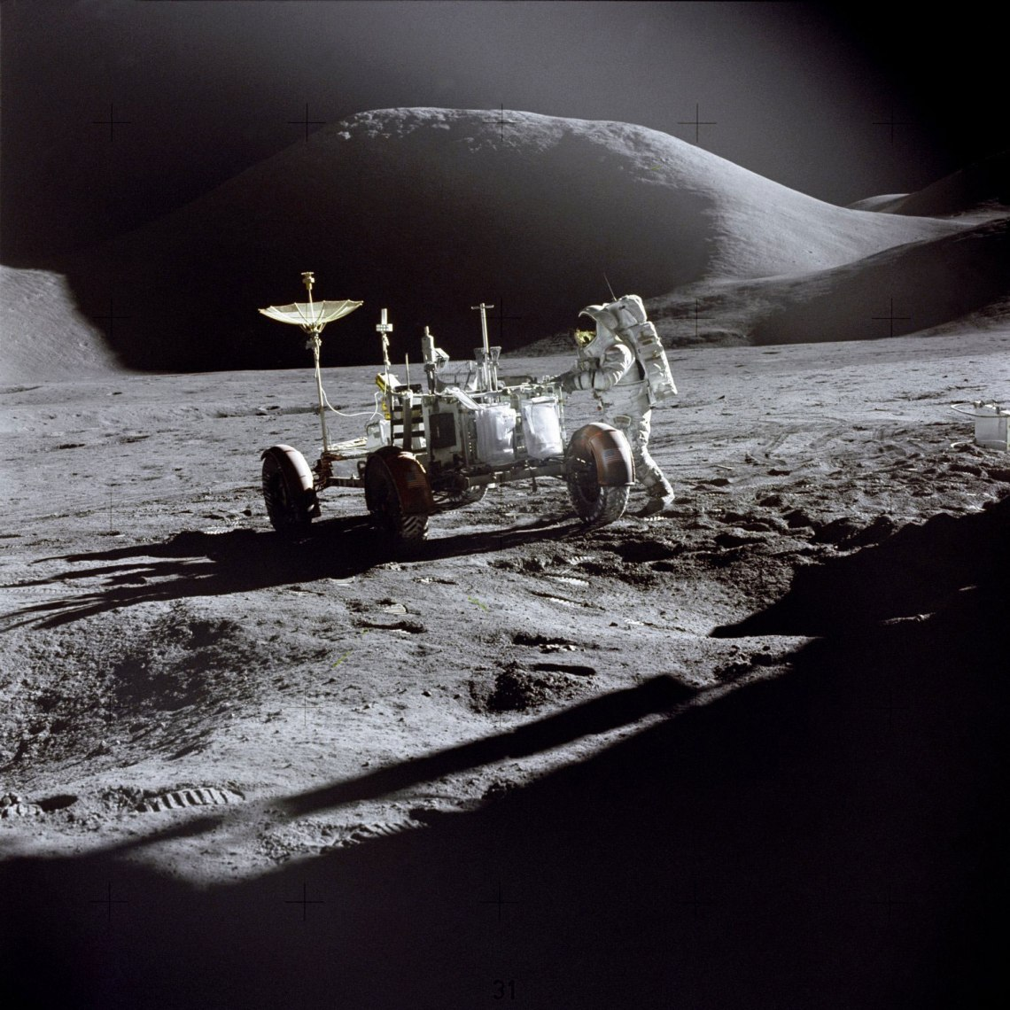 Jim Irwin is photographed beside the Lunar Roving Vehicle, with Mount Hadley in the background. Seen on the back of the Rover are two sample collection bags mounted on the gate, along with the rake, both pairs of tongs, the extension handle with scoop probably attached, and the penetrometer. Credit: NASA