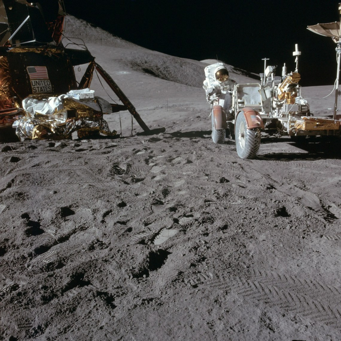 Jim Irwin works at the Lunar Roving Vehicle during the first EVA at the Hadley-Apennine landing site. A portion of the Falcon Lunar Module is on the left. The undeployed Laser Ranging Retro Reflector LR-3 lies atop the LM's Modular Equipment Stowage Assembly MESA. Credit: NASA via Retro Space Images