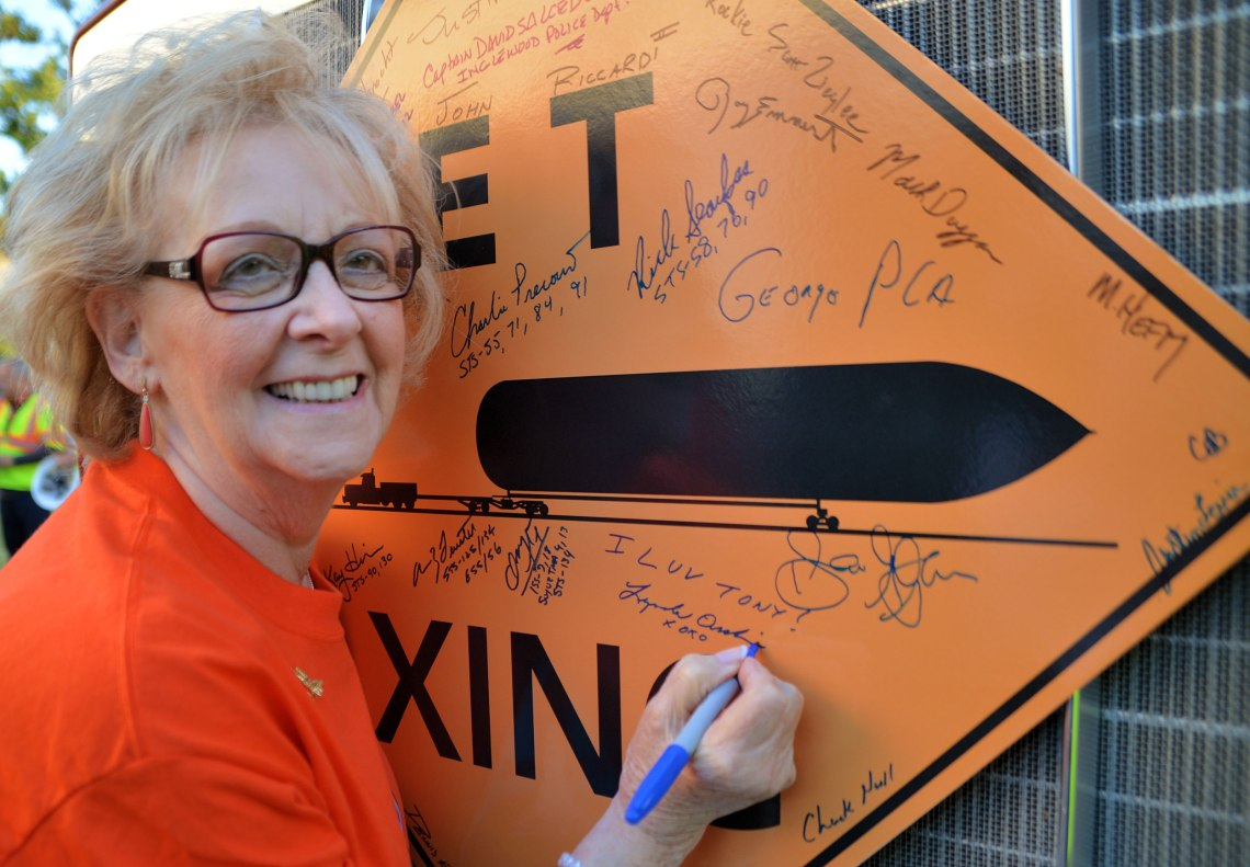 Mrs. Lynda Oschin signs an 'ET Xing' sign during the day's festivities. Credit: Julian Leek/JNN
