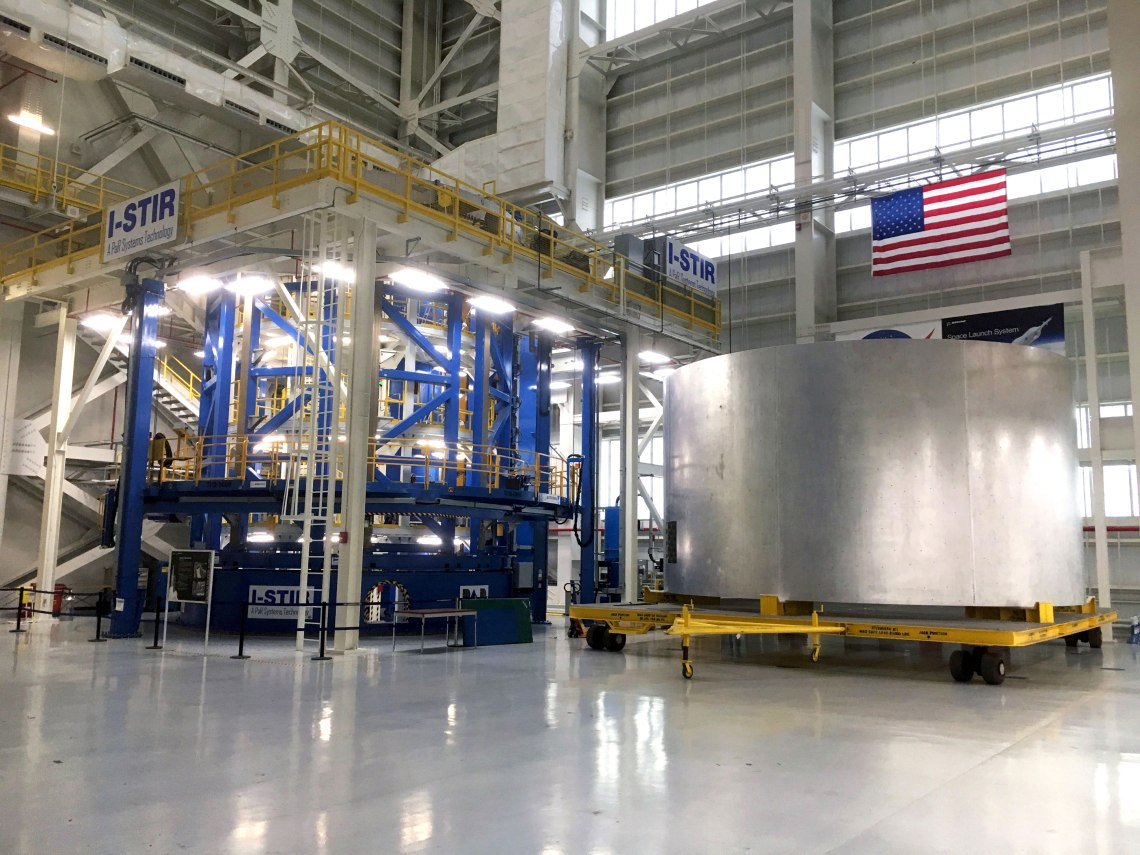 The Vertical Weld Center tool used to fabricate barrel segments for the SLS liquid hydrogen and oxygen core stage tanks via vertical friction stir welding operations at NASA's Michoud Assembly Facility in New Orleans. To the right of the welder is the weld confidence barrell. Credit: Chase Clark