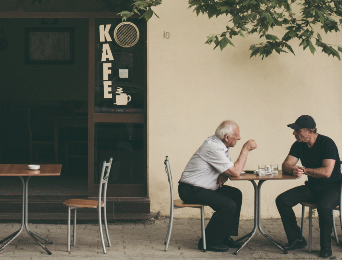 two men sitting outside chatting