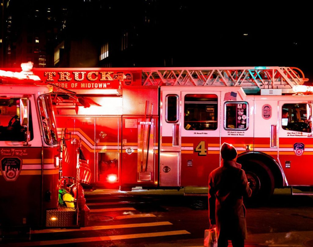 person standing near lighted firetruck