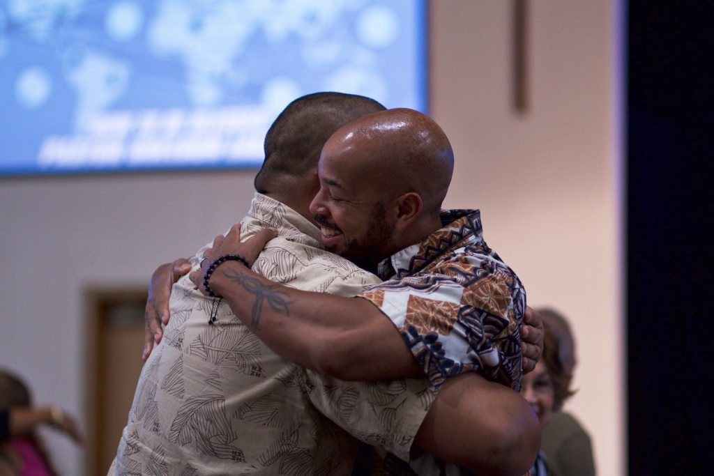 Two men hugging at church, greeting