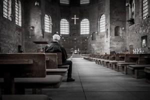 man sitting in an empty church