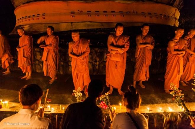Les moines tout au tour du chedi, attendent les offrandes disposées par les disciples