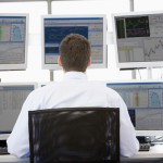 Stock Trader Looking At Multiple Monitors - Rockwell Trading
