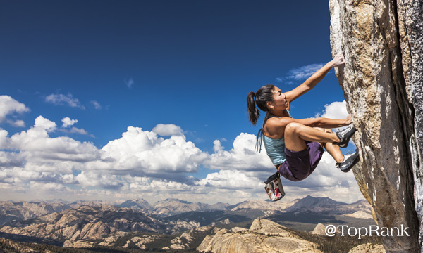 Woman rock climber scaling vertical wall.