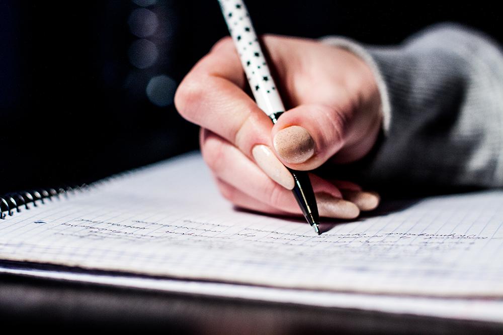 hand met pen wat skryf op notaboek