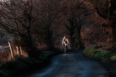 Bicycles in the landscape series - a cyclist in a yellow top emerges from the shadows of a country lane at sunrise