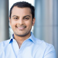 Closeup headshot portrait happy handsome business man smiling in blue shirtconfident and friendly on isolated office interior background. Corporate success
