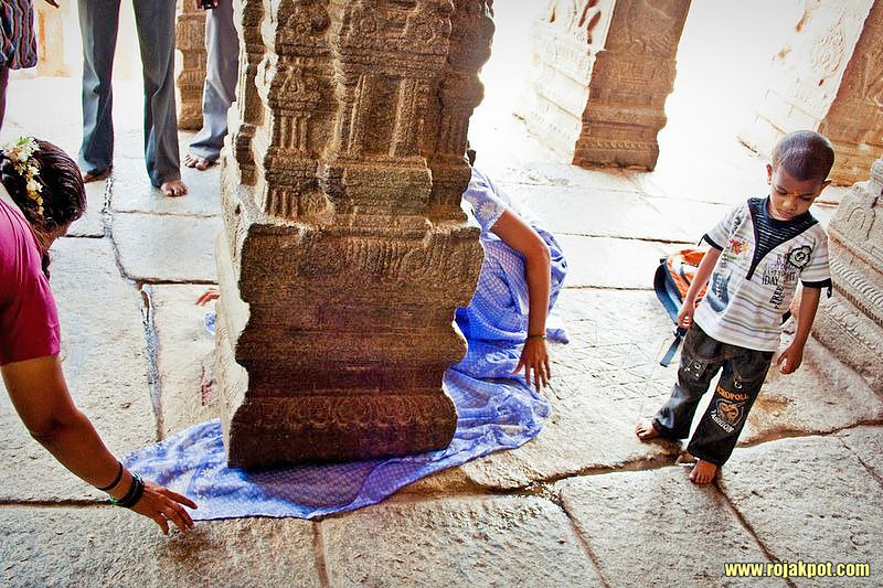 Two ladies passing a saree cloth underneath the hanging pillar of Lepakshi Temple