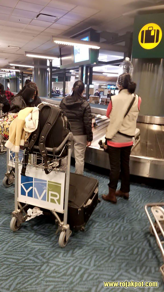 Lady wearing water bottle in Vancouver International Airport