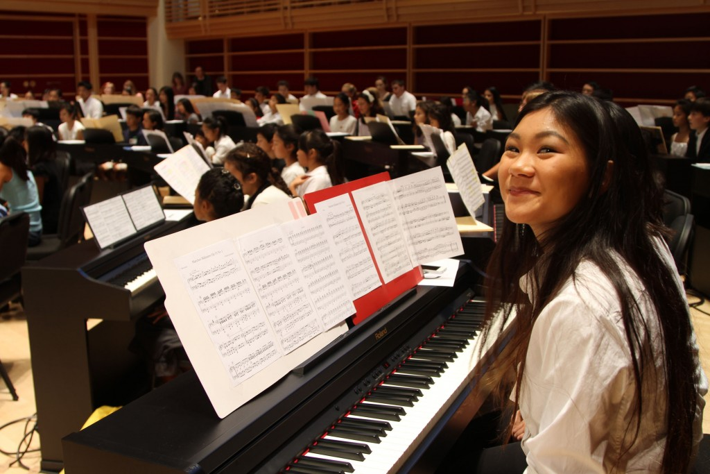 Students playing Roland pianos enjoying unique concert experience.