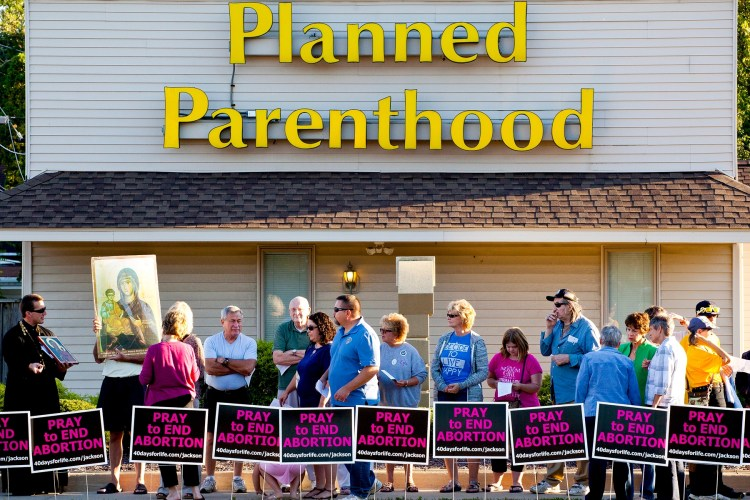 People protest outside of Planned Parenthood on Wednesday, Sept. 23, 2015, in Jackson, Mich. Participants sang and prayed to end abortion and close Planned Parenthood.