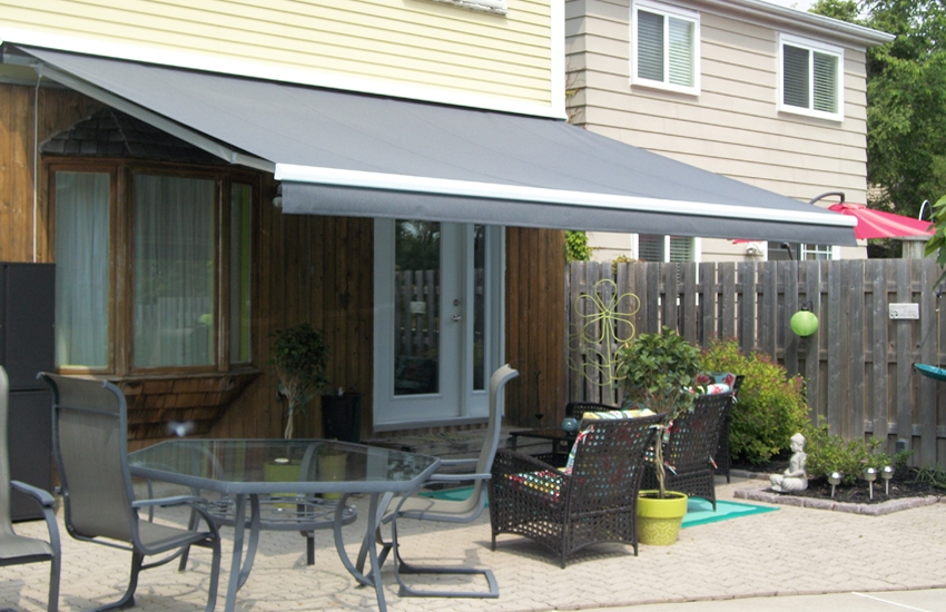 Solid grey awning by the pool side  Rolltec Retractable