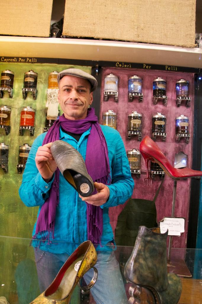 Uomo vestito con colori sgargianti e scoppola in testa, tiene in mano una sua creazione di scarpa fatta con le chiusure lampo.