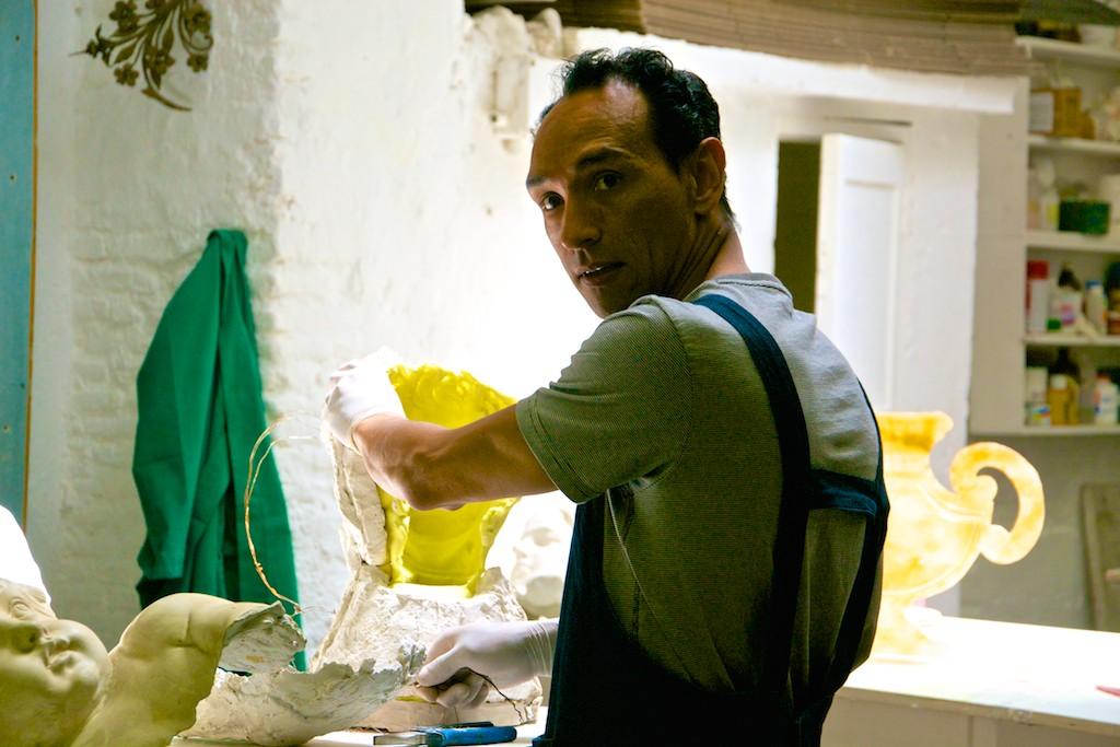 Uomo giovane che fa un calco in gesso del viso di un angelo e con sguardo intenso guarda la telecamera.