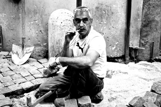 Uomo di 60 anni seduto perterra con sampietrini intorno e un martello vicino piantato sulla sabbia fa una pausa fumando una sigaretta elettronica. Indossa una maglietta bianca con un puma nero davanti.