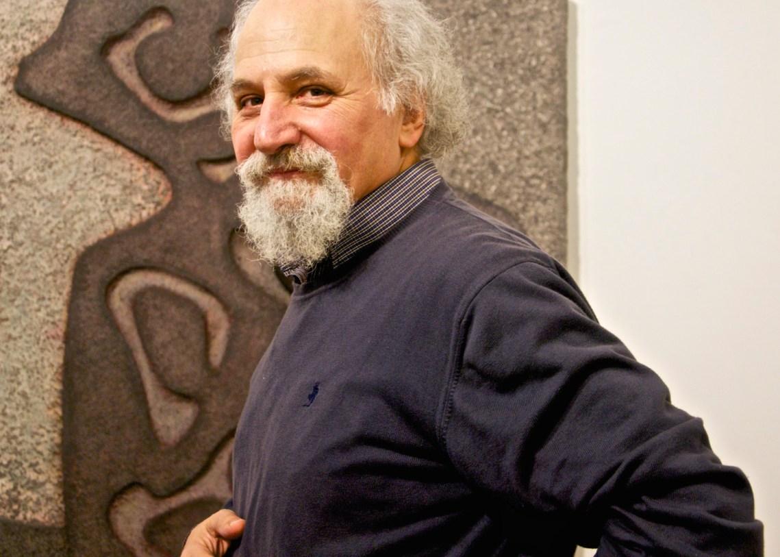 Uomo con barba e capelli bianchi con maglione ble davanti ad una sua opera di finta pietra.
