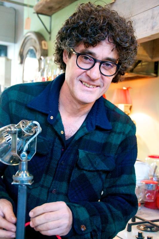 Uomo con capelli scuri e ricci, occhiali da vista rotondi con camicia a quadri blu e verde sorride tenendo in mano una lampada creata con materiale riciclato.