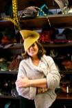 Donna sorridente indossa un cappello giallo molto estroso con piume.