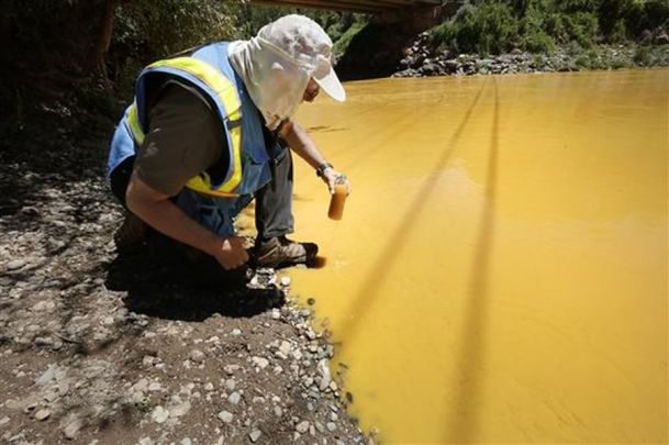 Dan Bender, with the La Plata County Sheriff's Office, takes a water sample from the Animas River near Durango, Colo., Thursday, Aug. 6, 2015. The U.S. Environmental Protection Agency said that a cleanup team was working with heavy equipment Wednesday to secure an entrance to the Gold King Mine. Workers instead released an estimated 1 million gallons of mine waste into Cement Creek, which flows into the Animas River. (Jerry McBride/The Durango Herald via AP) MANDATORY CREDIT