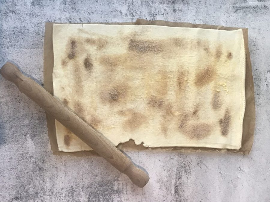 Image of puff pastry sprinkled with cinnamon and sugar with rolling pin