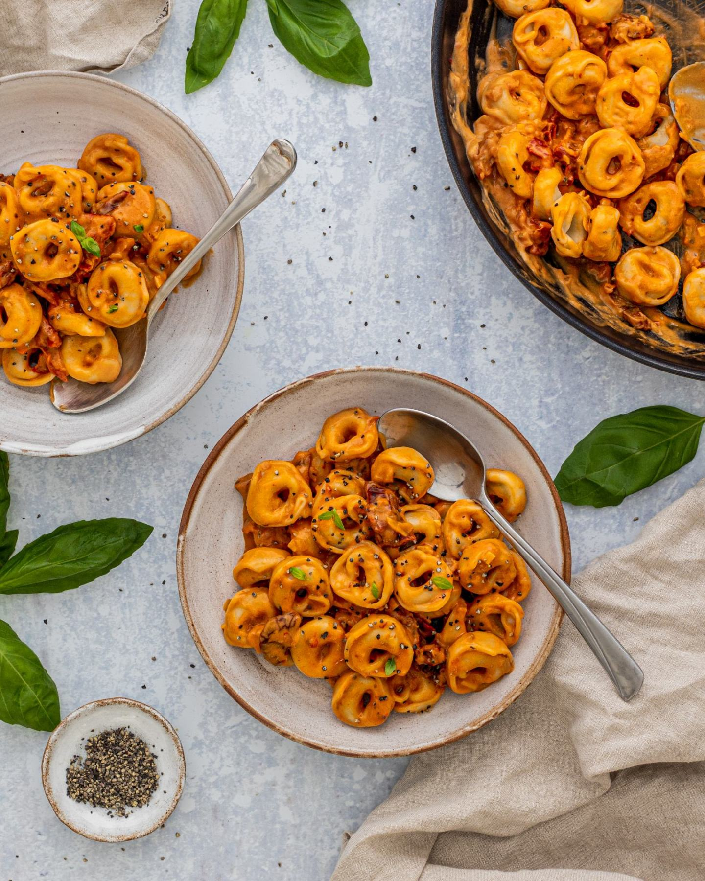 Creamy Sun-Dried Tomato Pasta - Vegan Tortellini served onto 2 plates with the pan standing next to it on a bright table top