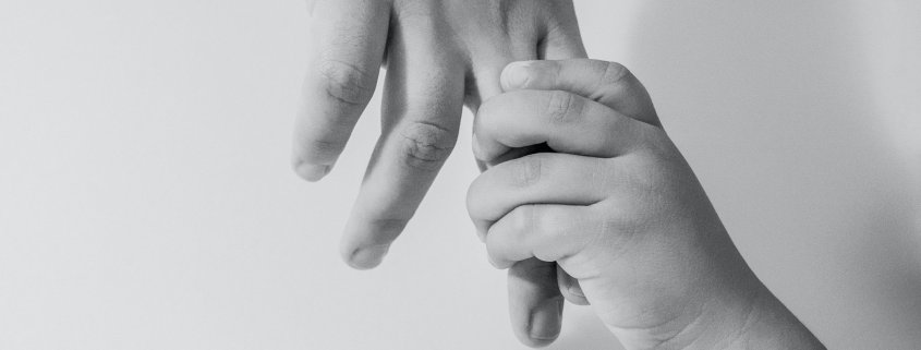 black and white photo of child's hand holding mother's
