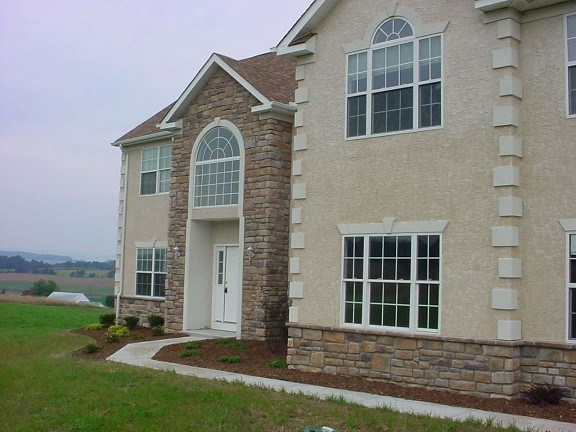 Natural stone siding cost vs stucco and brick veneer for Brick home construction costs
