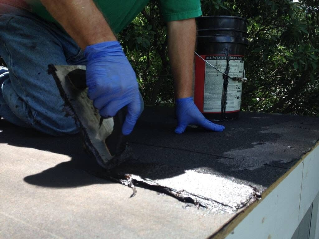 Minimum Roof Pitch for Shingles - Man Applying Tar to a Roof
