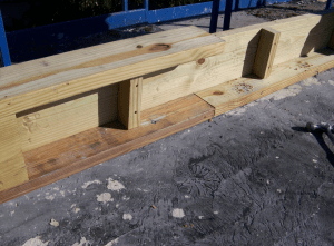 The perimeter wood blocking was prefabricated and assembled offsite from pressure-treated 2- by 6-inch and 2- by 8-inch wood in a knee-wall configuration installed in 10-foot lengths. Doing so reduced the total quantity of blocking used on the project by nearly half (approximately 2,000 board-foot savings compared to installing multiple layers of blocking). The bottom blocking layer was anchored to the steel framing at 16-inch on-center intervals.