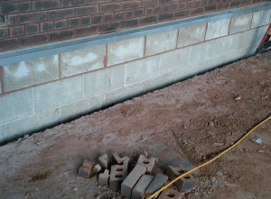 PHOTO 4: Instead of the construction in Photo 3, here, concrete masonry units were installed below the counterflashing receiver. If ever exposed, CMU will readily take on water. CMU walls also can excessively absorb adhesives and two applications are recommended.
