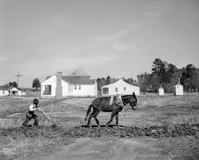 Plowing a field at Palmerdale Homestead. Pinson, Alabama.New homestead in the background. 1937.