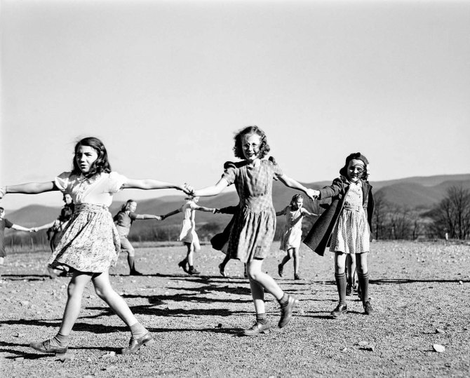 Children playing a singing game during afternoon play periodat Tygart Valley Homestead school. Near Daily, West Virginia. 1941.
