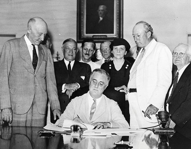 FDR signing the Social Security Legislation with Frances Perkins and members of Congress, August 14, 1935.