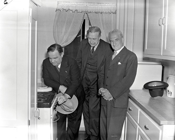 Modern kitchen in the Kingsborough Houses with Mayor LaGuardia and Gerard Swope, Chair of NYCHA. 1941.