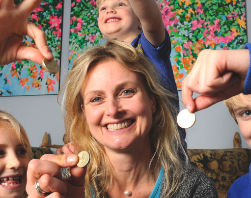 A smiling family of a Mum and three children each holding up a coin, sitting in a living room with origami shapes overlaid decorating the corners