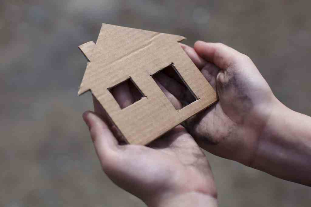 A pair of hands holding a cardboard cutout of a house