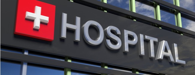 "A close-up of a black sign on a building that says ""Hospital"" in gray letters. Next to the text is a red square with a gray cross symbol on it."