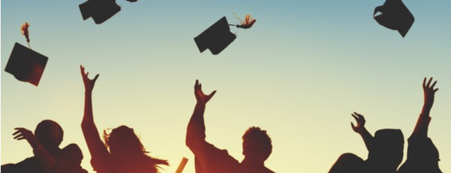 A group of people, all silhouettes, throw graduation caps in the air in a celebratory fashion. They are backlit by the glow of sunlight.