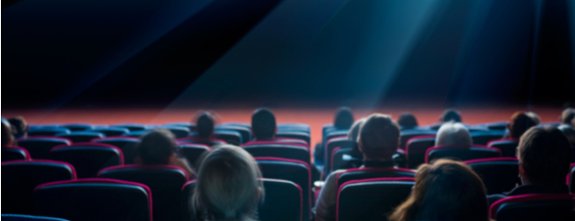 People in a movie theater, sitting in seats. The photo is from behind so you can only see the backs of heads.