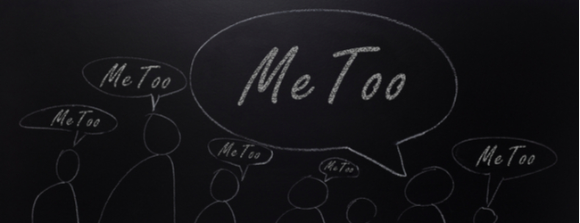 "A blackboard with outlines of people all with speech bubbles that read ""me too."""