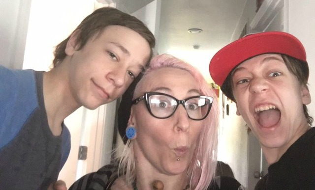 Photo of Maggie Winston, a white woman with light pink hair and glasses, in between her two sons, both teenage.