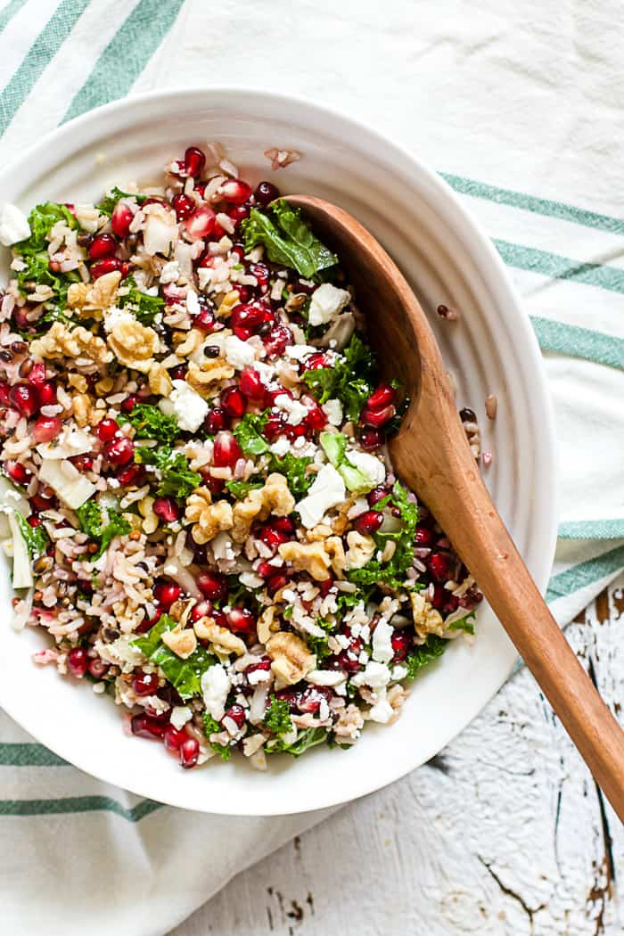 Wild Rice and Pomegranate Salad - A delicious grain-based salad with wild rice, pomegranates, feta, walnuts, kale, red onions, basil, and orange champagne vinaigrette. Perfect for make-ahead lunches and potlucks! | rootsandradishes.com